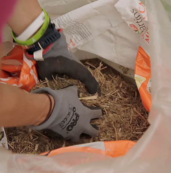 greening-the-garden-hands-grabbing-mulch-from-bag