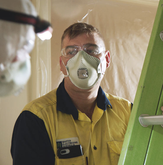 A man wearing a mask while doing renovations in a Port Pirie home